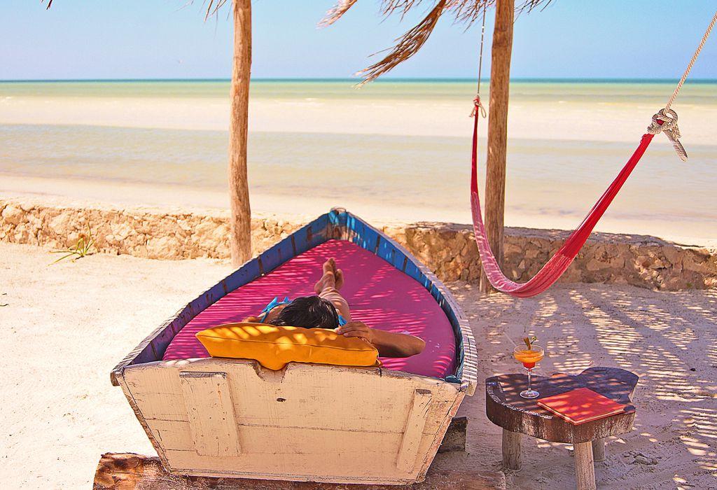 mujer camastro frente a la playa holbox