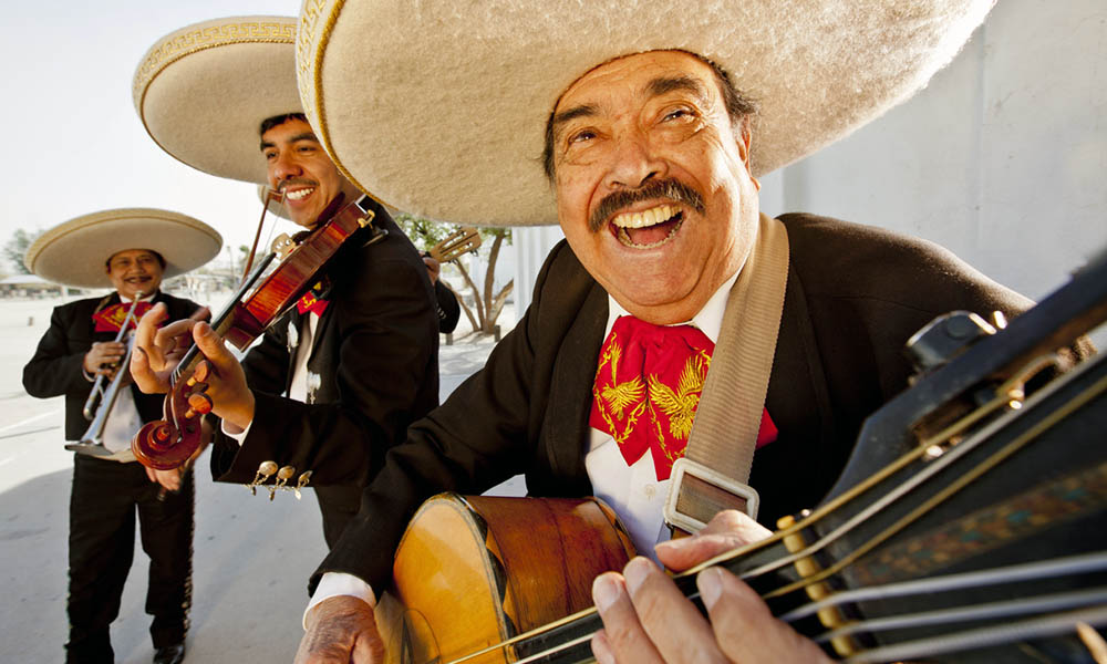 Three smiling members of a mariachi band